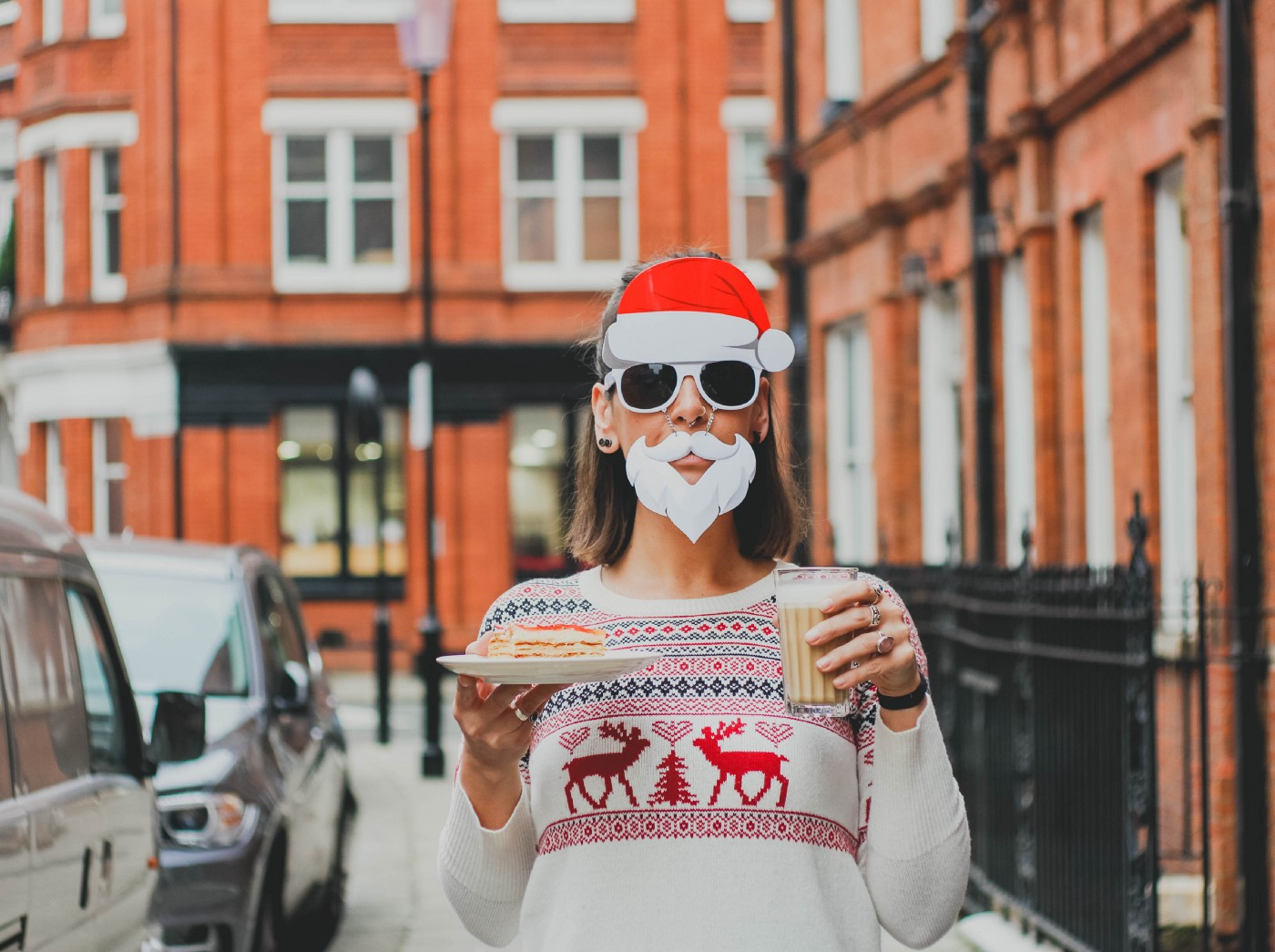 Woman in holiday sweater, sunglasses, and Santa hat and beard holds a holiday drink and plate of cookies on a city street.