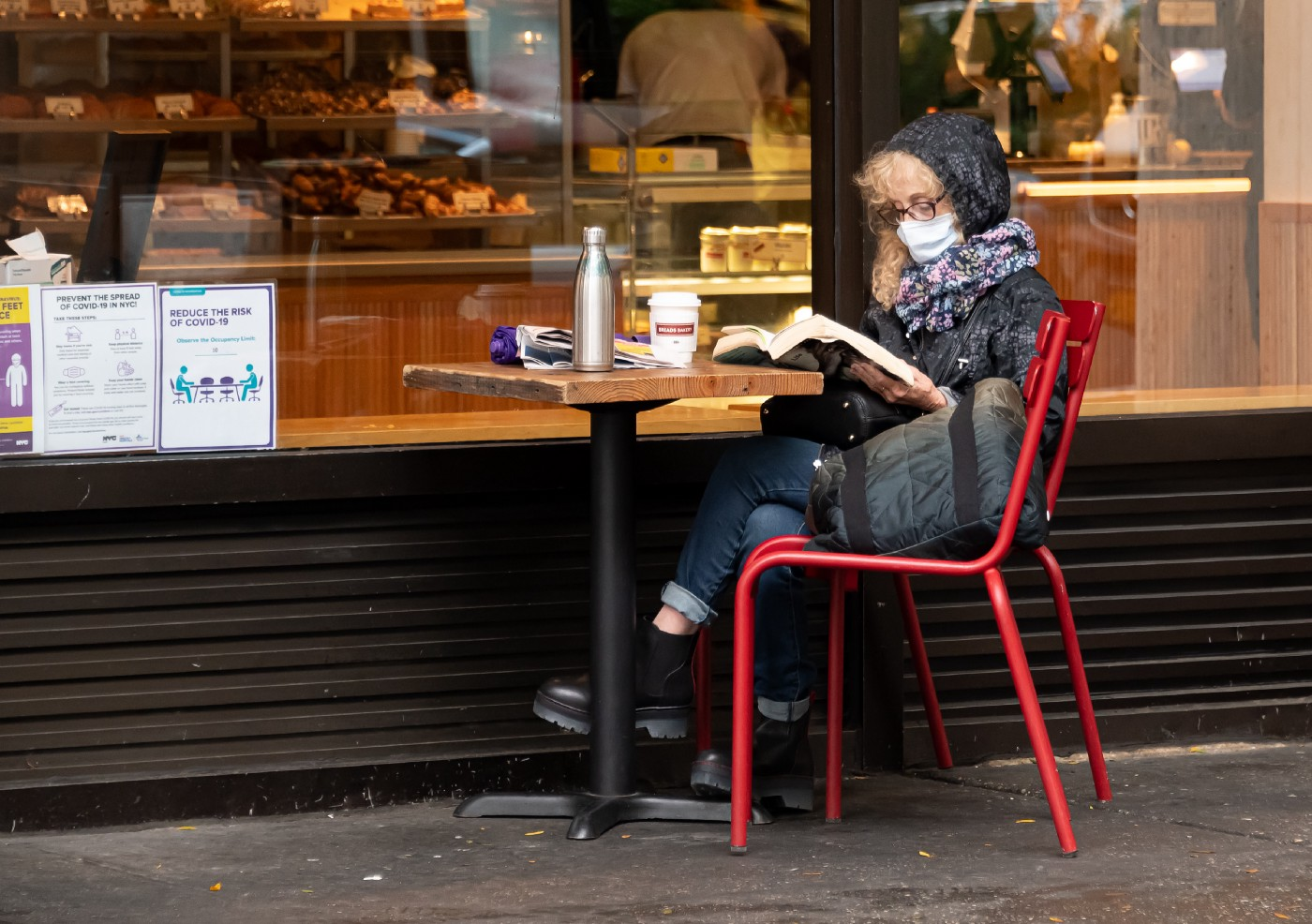 Older woman wearing face mask reading a book outside a cafe.