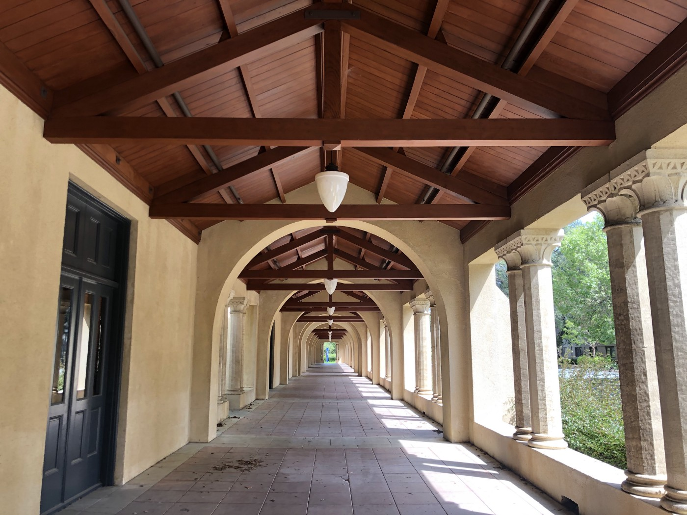 photo down the length of a covered arcade with repeating architectural features