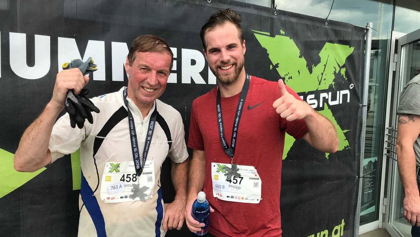 Two men celebrate with medals after completing the X Cross Run.