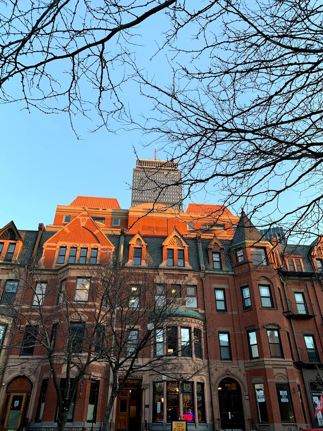 Brownstone buildings and a high-rise at sunset
