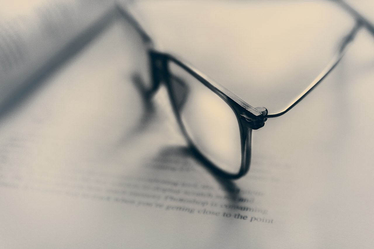 The photograph shows reading glasses placed on a page of a book.
