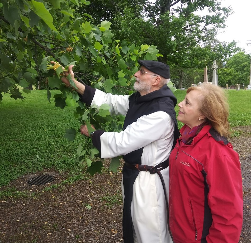 Brother Paul Quenon and Judith Valente stop to observe a yellow blossom on a tulip poplar tree at the Abbey of Gethsemani in Kentucky.