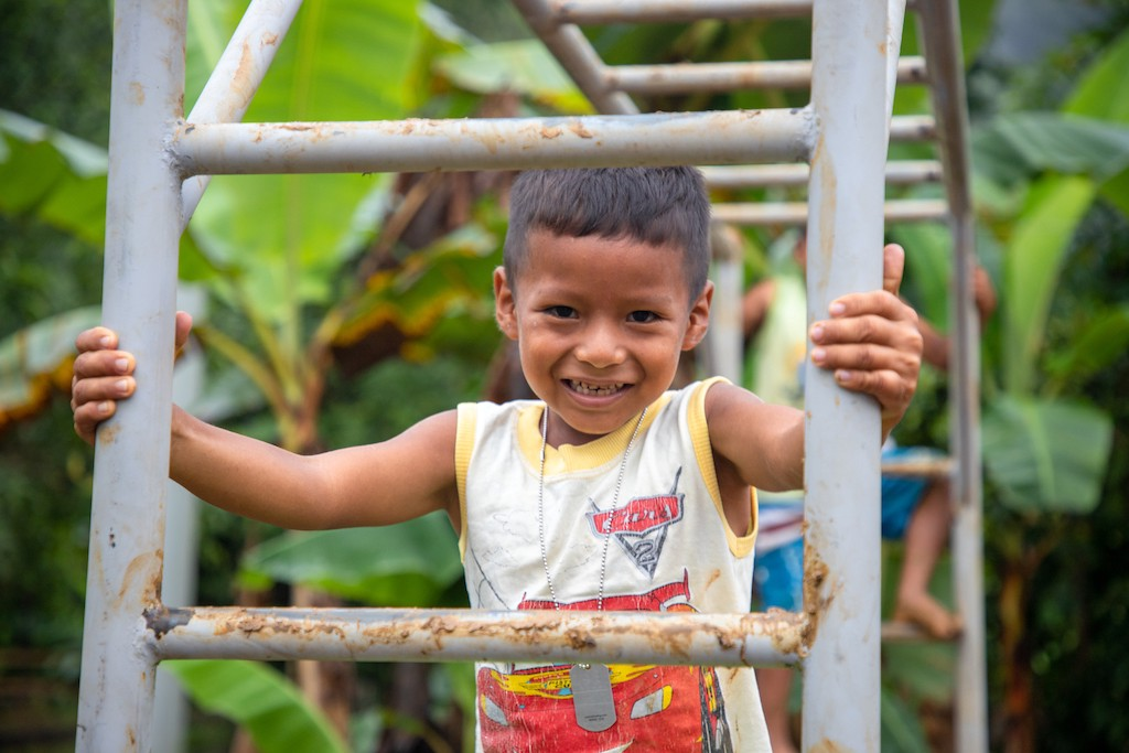 A boy from the Chachi tribe in Ecuador, smiling at the camera from behind a playground ladder.
