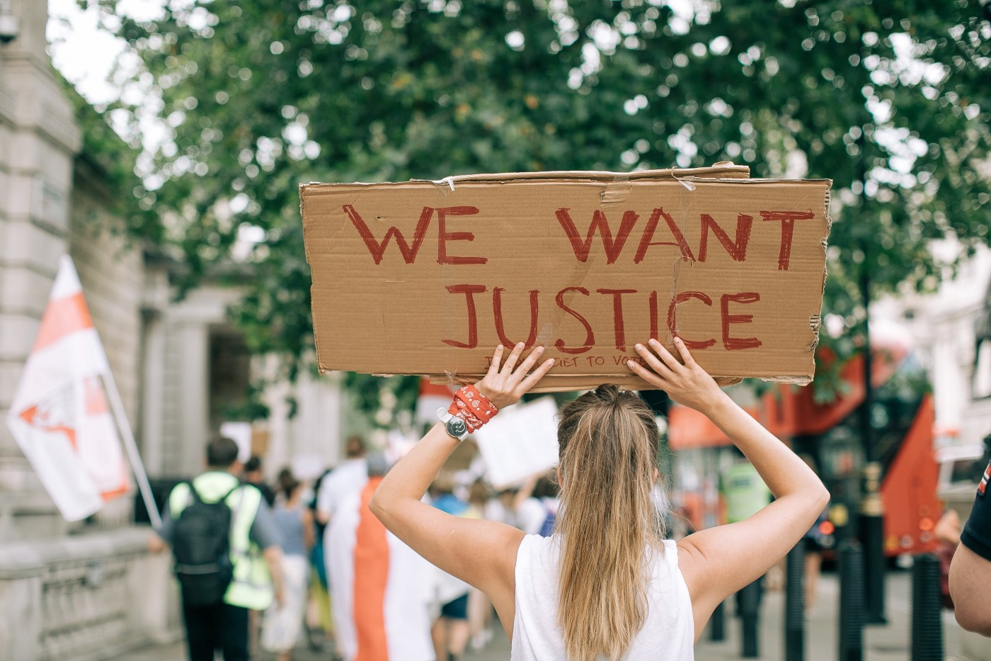 "A protestor holding a sign that says ""We Want Justice"""