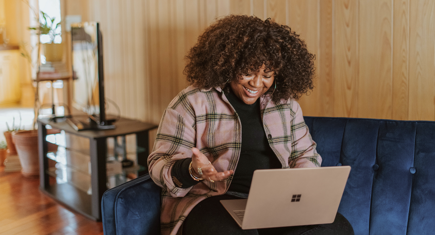 Photo by Surface on Unsplash—Woman with curly hair sitting on blue couch, smiling and gesturing to an open laptop computer on her lap