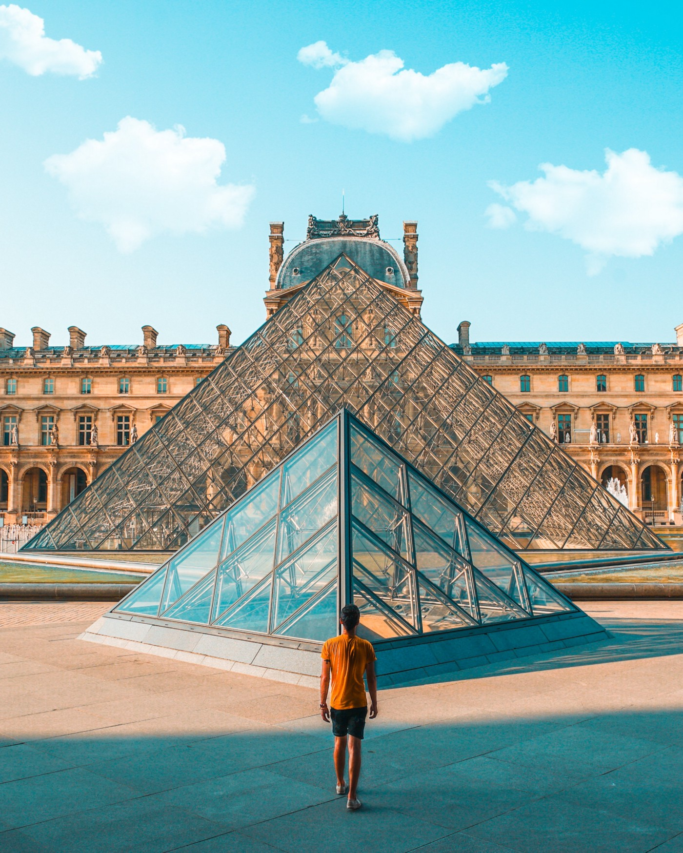 Man standing in front of two glass pyramids. These pyramids form the outside of the Louvre museum in France.