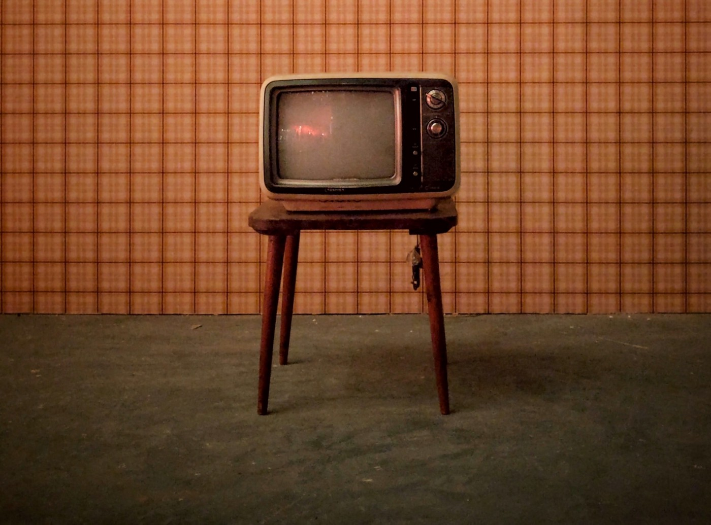 Vintage TV on a wooden table. Gray carpet underneath and a plaid striped background.