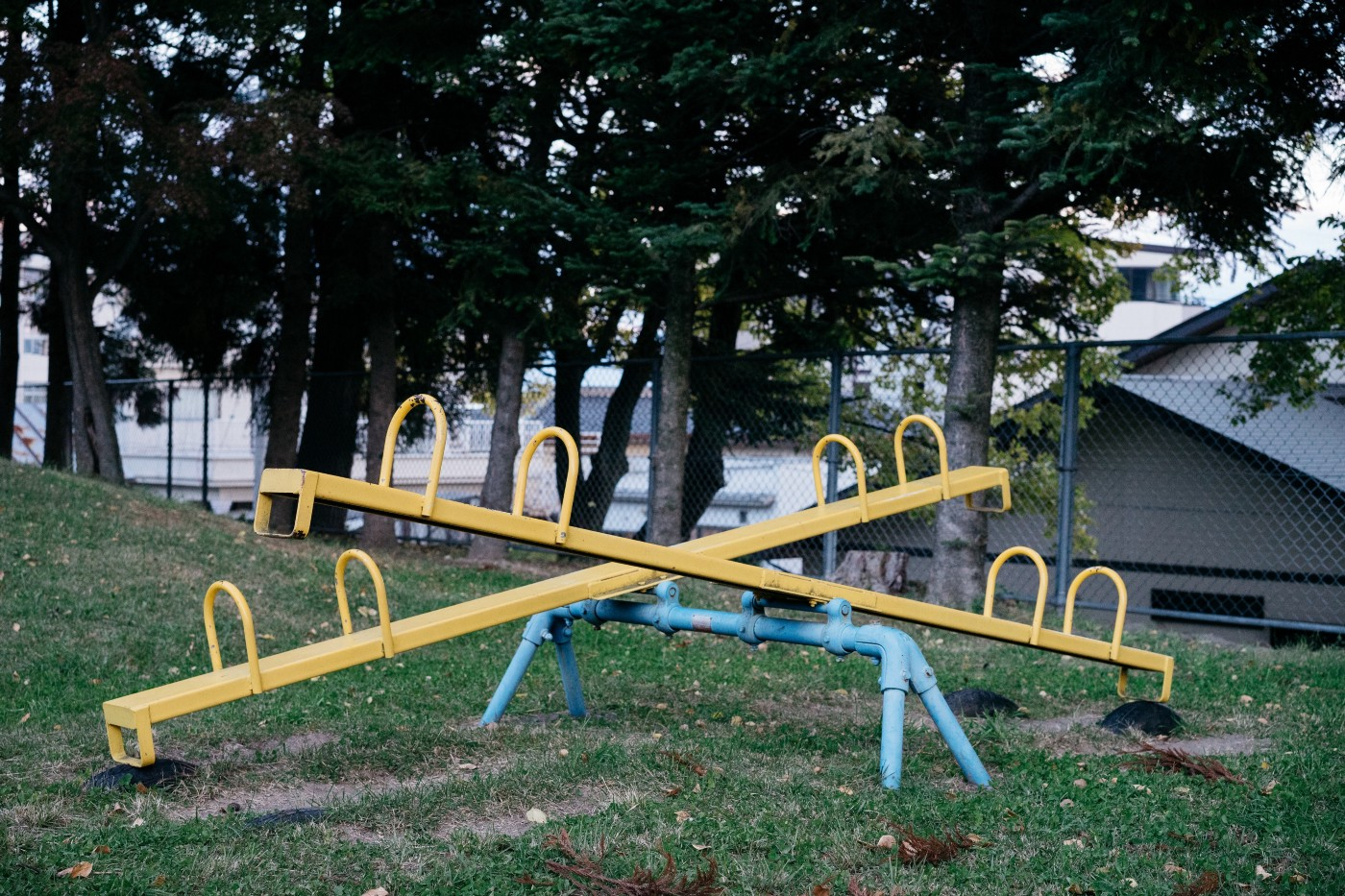 Two yellow metal seesaws on a powder blue base in a park