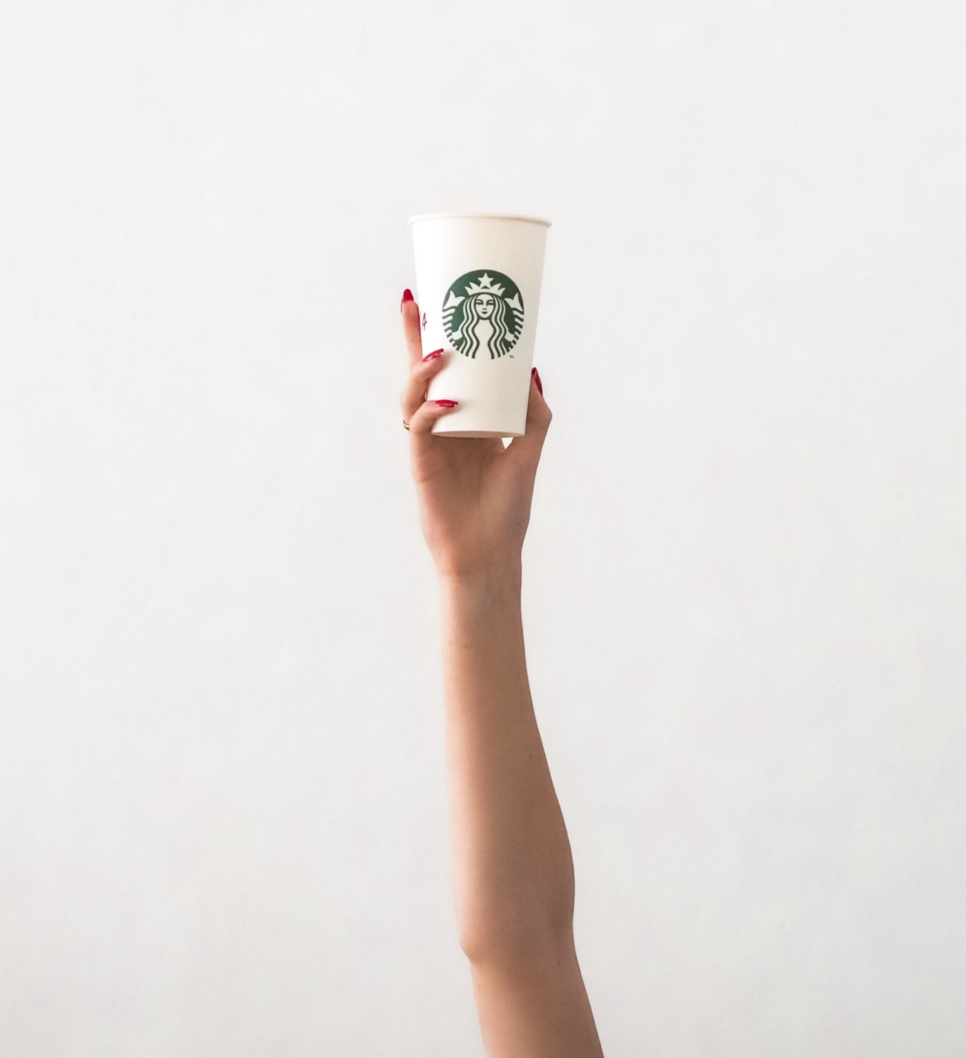 A feminine hand thrusting a Starbucks cup up into the air.