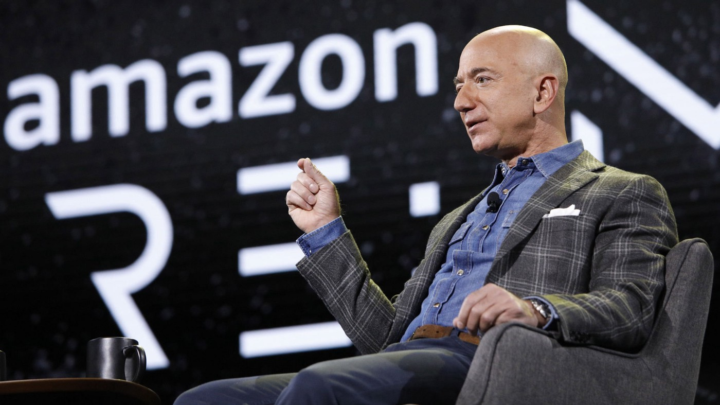 Jeff Bezos seated in a chair with the Amazon logo behind him.