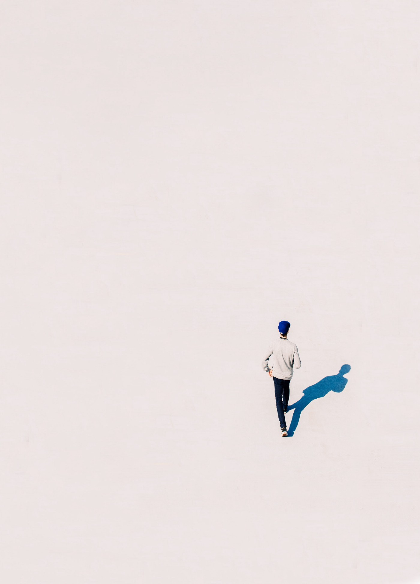 the viewpoint is from above and we can see a man walking in plain white background, his shadow is blue