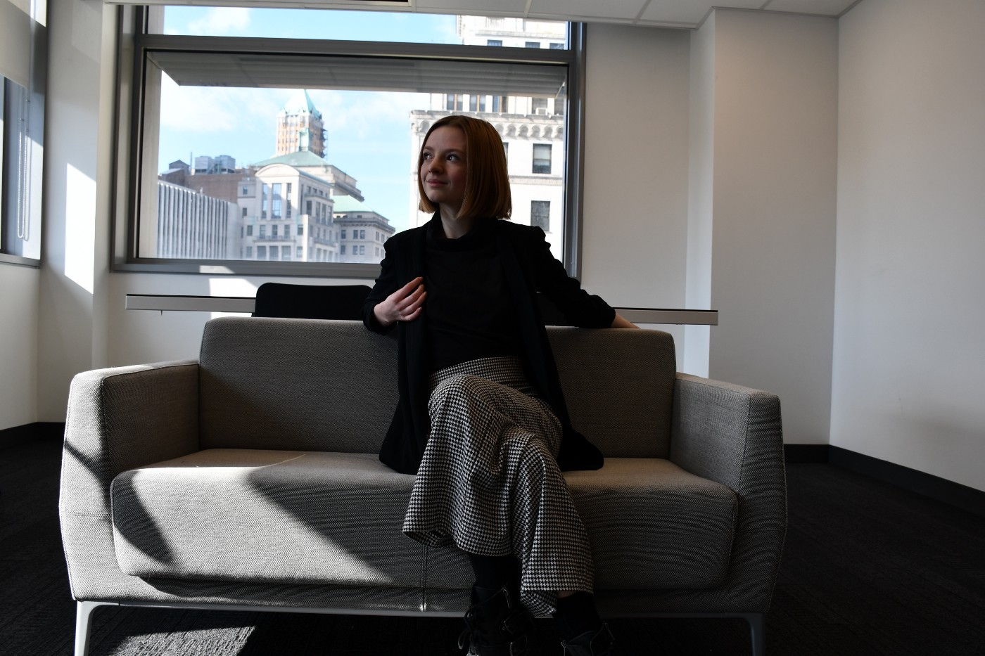 A blonde white woman sitting on a grey couch in front of a window.