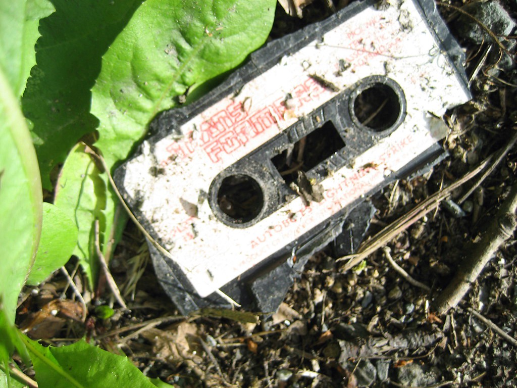 An old cassette tape thrown away in the dirt