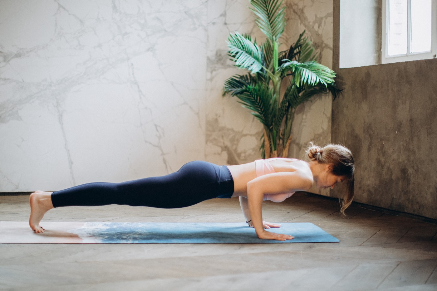 A woman doing a pushup on a yoga mat