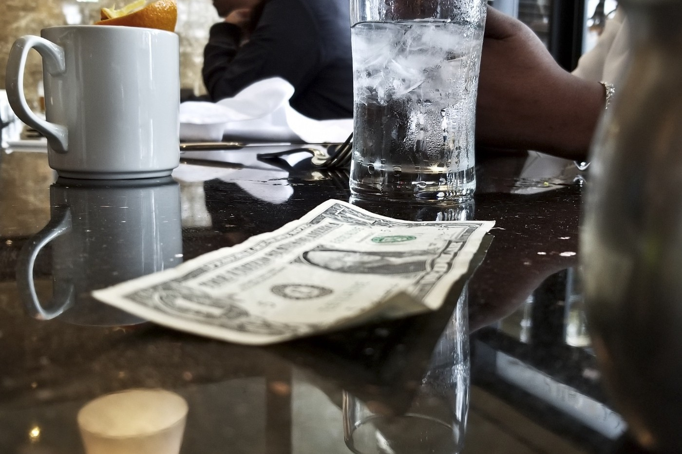 A close up of a dollar bill on a coffee table, next to a coffee mug and a glass of water.