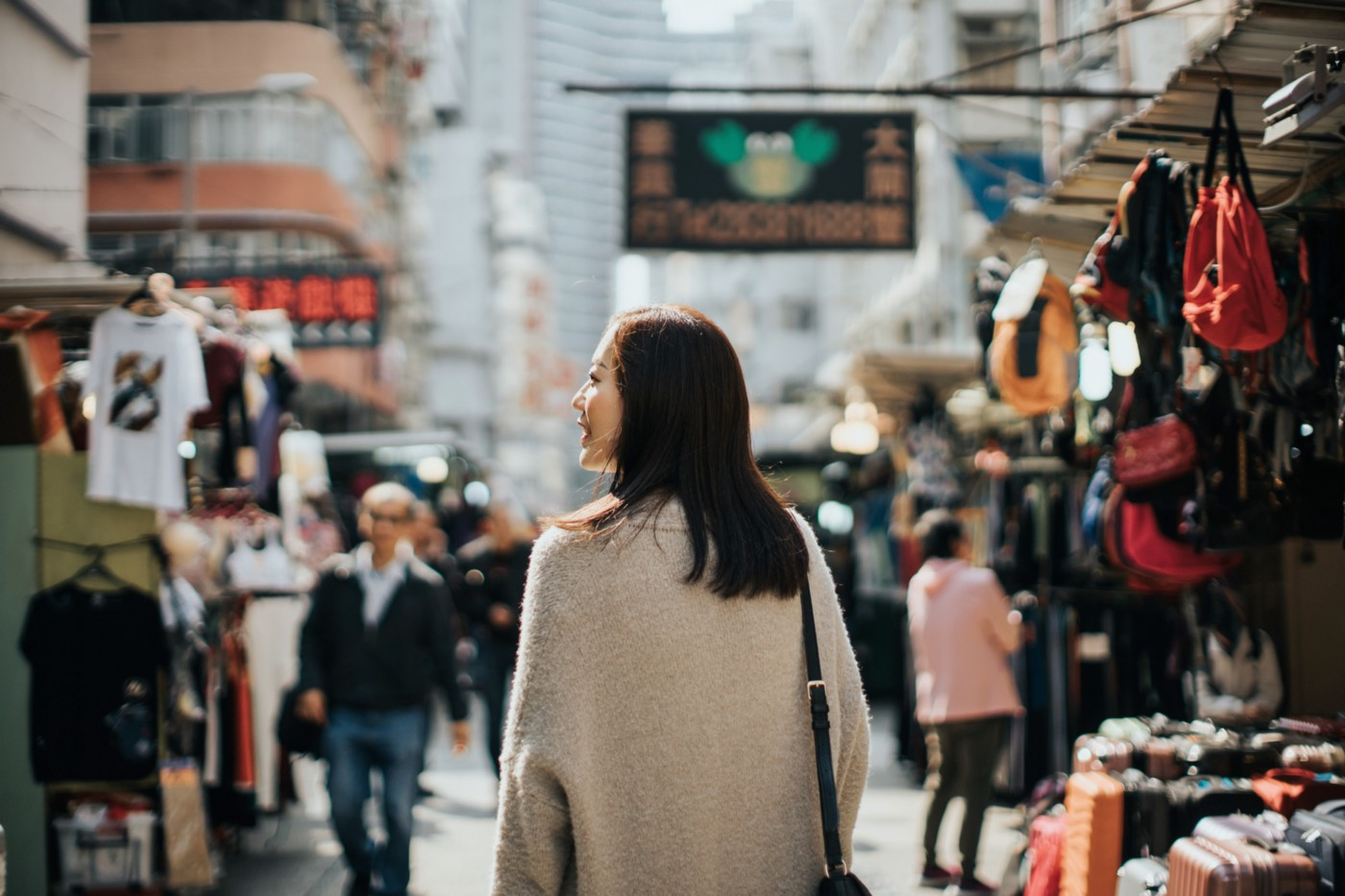 A photo of the back of a young Asian woman walking through a local market street in Hong Kong.