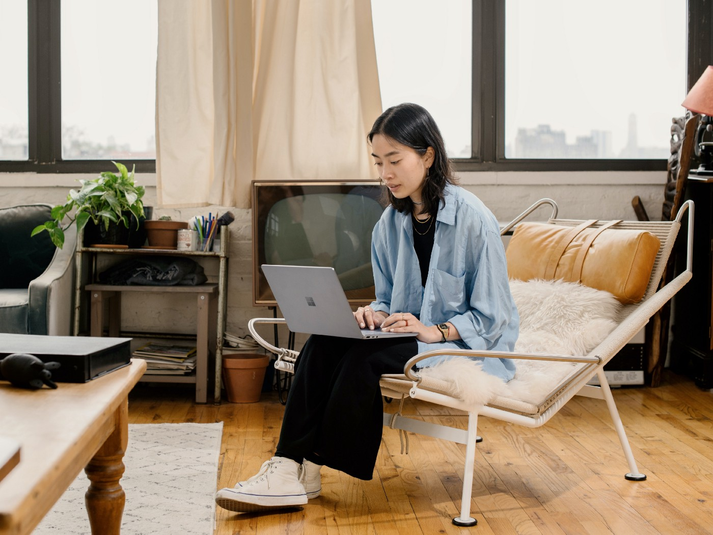 Girl with black hair wits in a chair with a fuzzy pillow while working on her laptop.