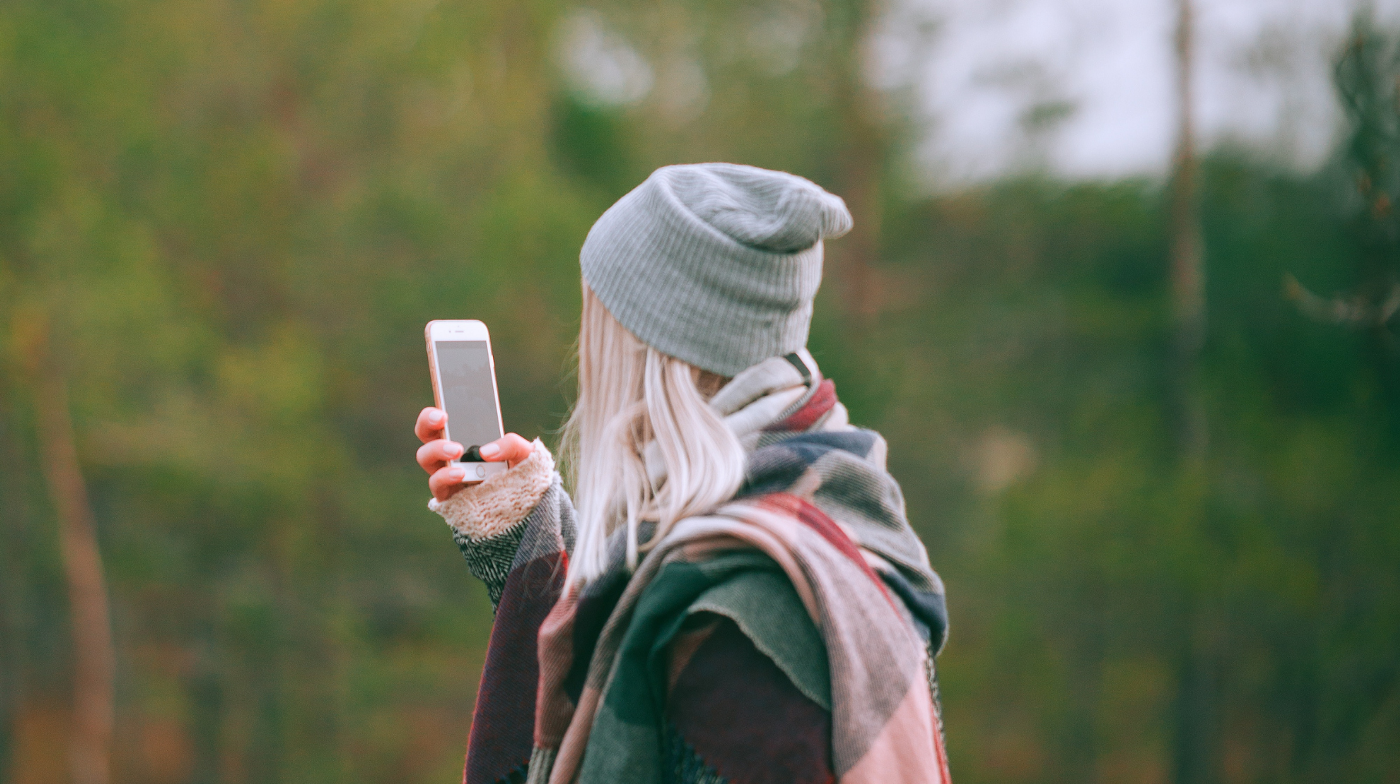 Photograph of back of woman with blonde hair who is outdoors, wearing fashionable winter clothes and holding up her cell phone