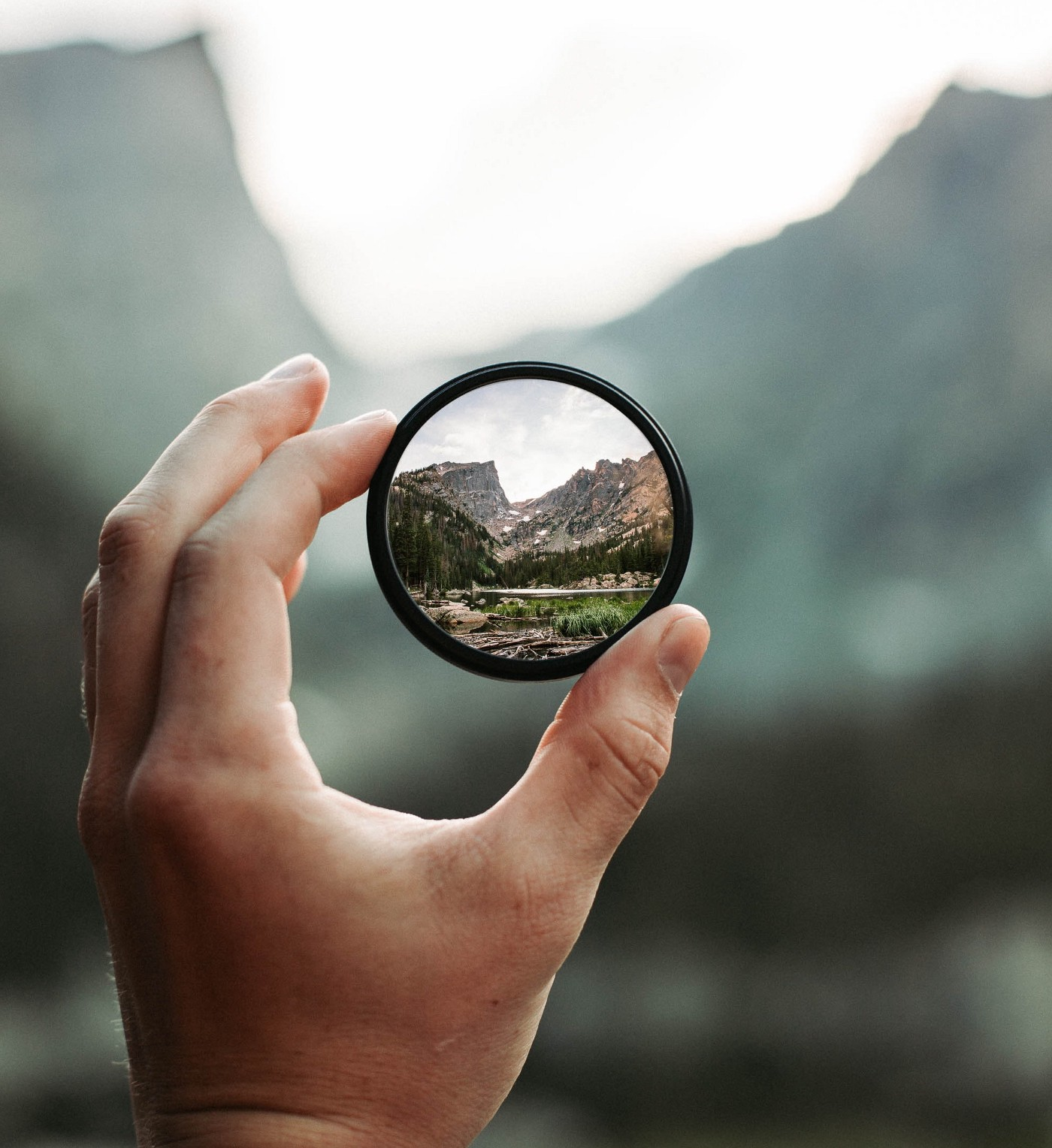 A hand holds up a magnifying glass to bring a lush, green landscape into focus.
