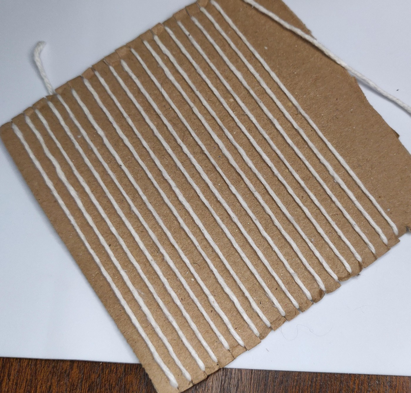 A mostly warped cardboard loom viewed from the front