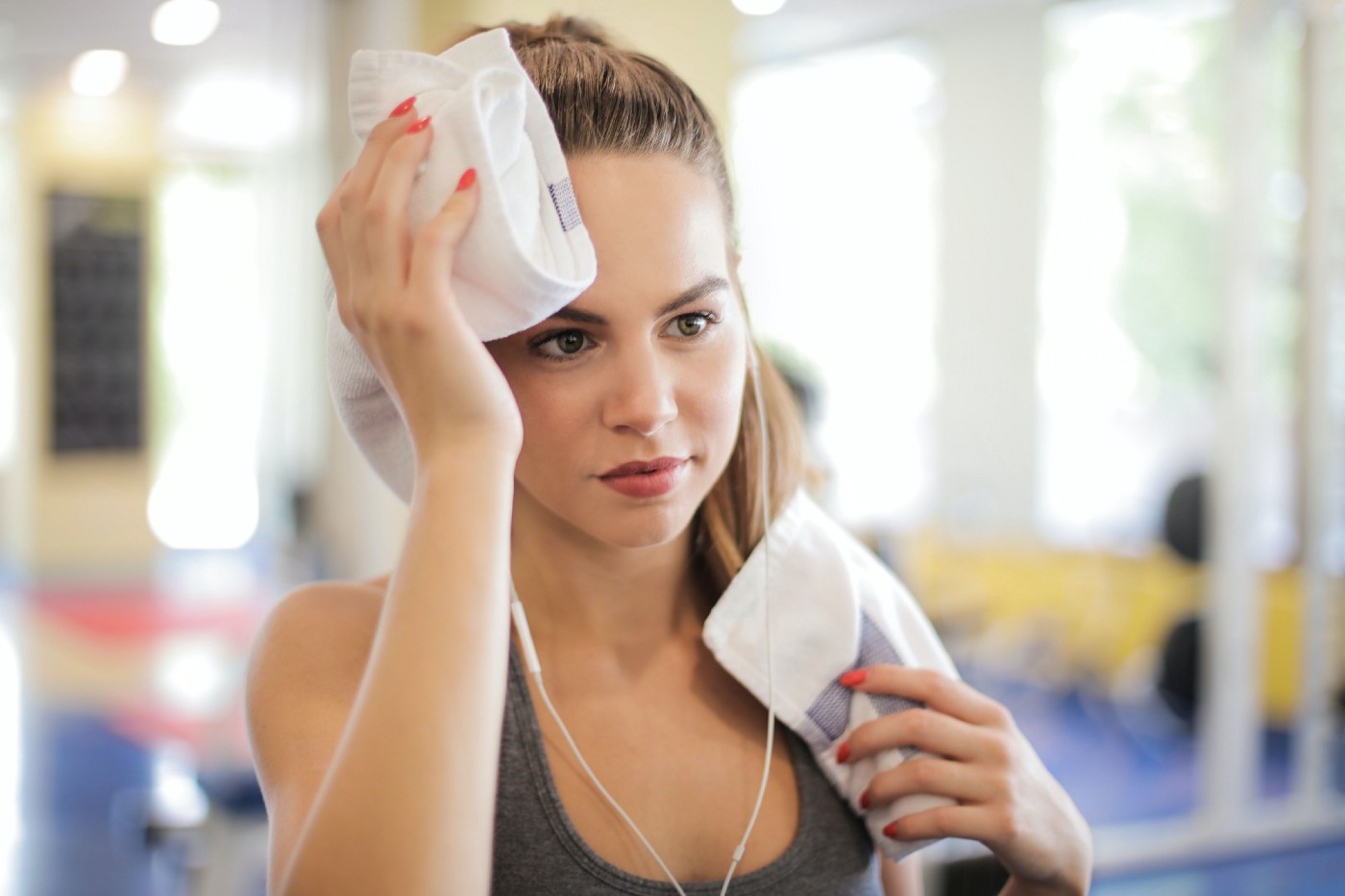 Young woman at the gym wiping her forehead with a small towel.