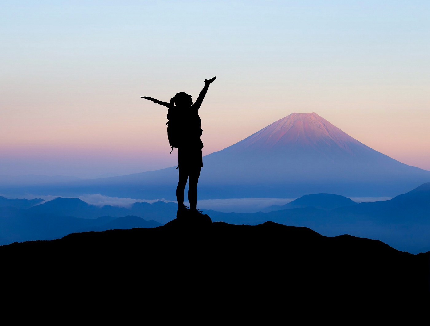 Woman on mounitain, view on another mountain, arms in the air