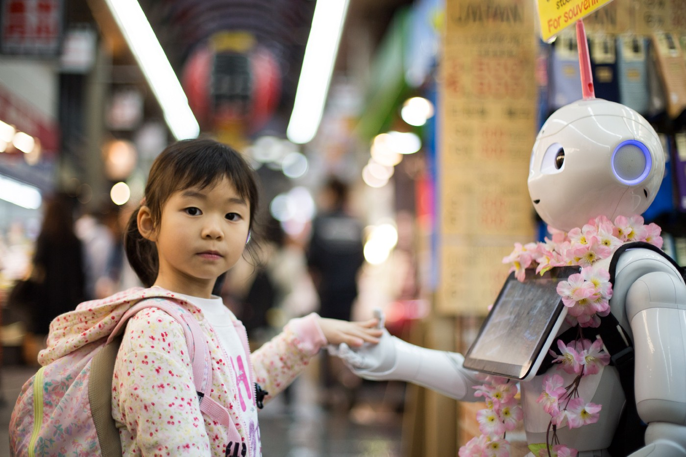 A child with a backpack reaches out to touch the hand of a social robot wearing a wreath of flowers