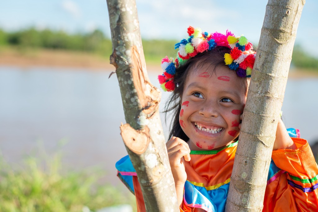 A girl from the Shawi tribe, wearing her traditional clothing and standing behind tree branches.