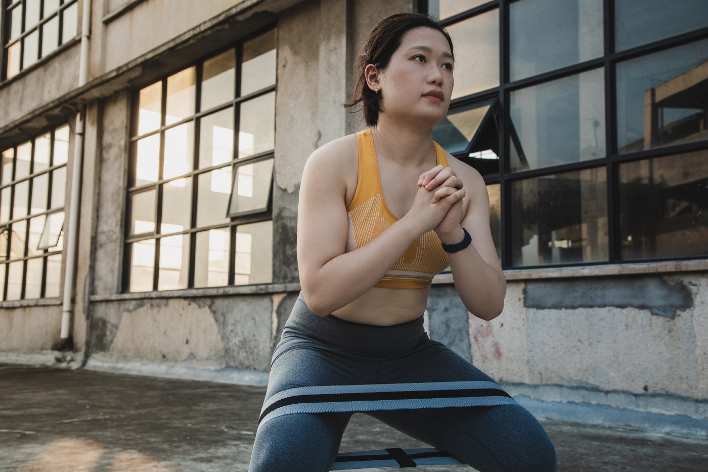 A young, Asian woman performing a squat exercise with a resistance band