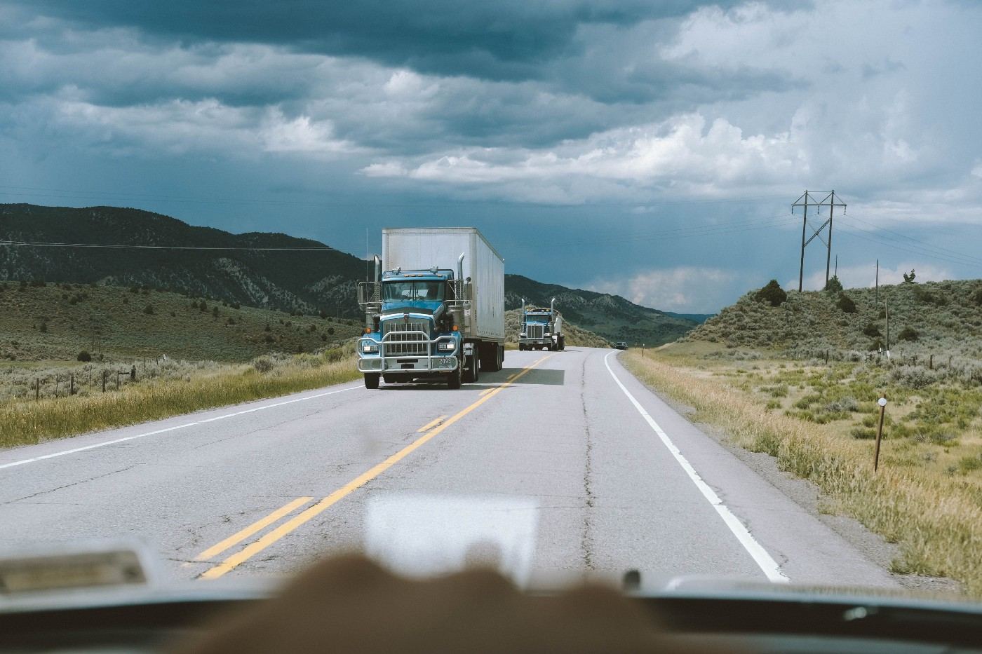 Two semi trucks drive down a highway to deliver their shipments while a car watches them.