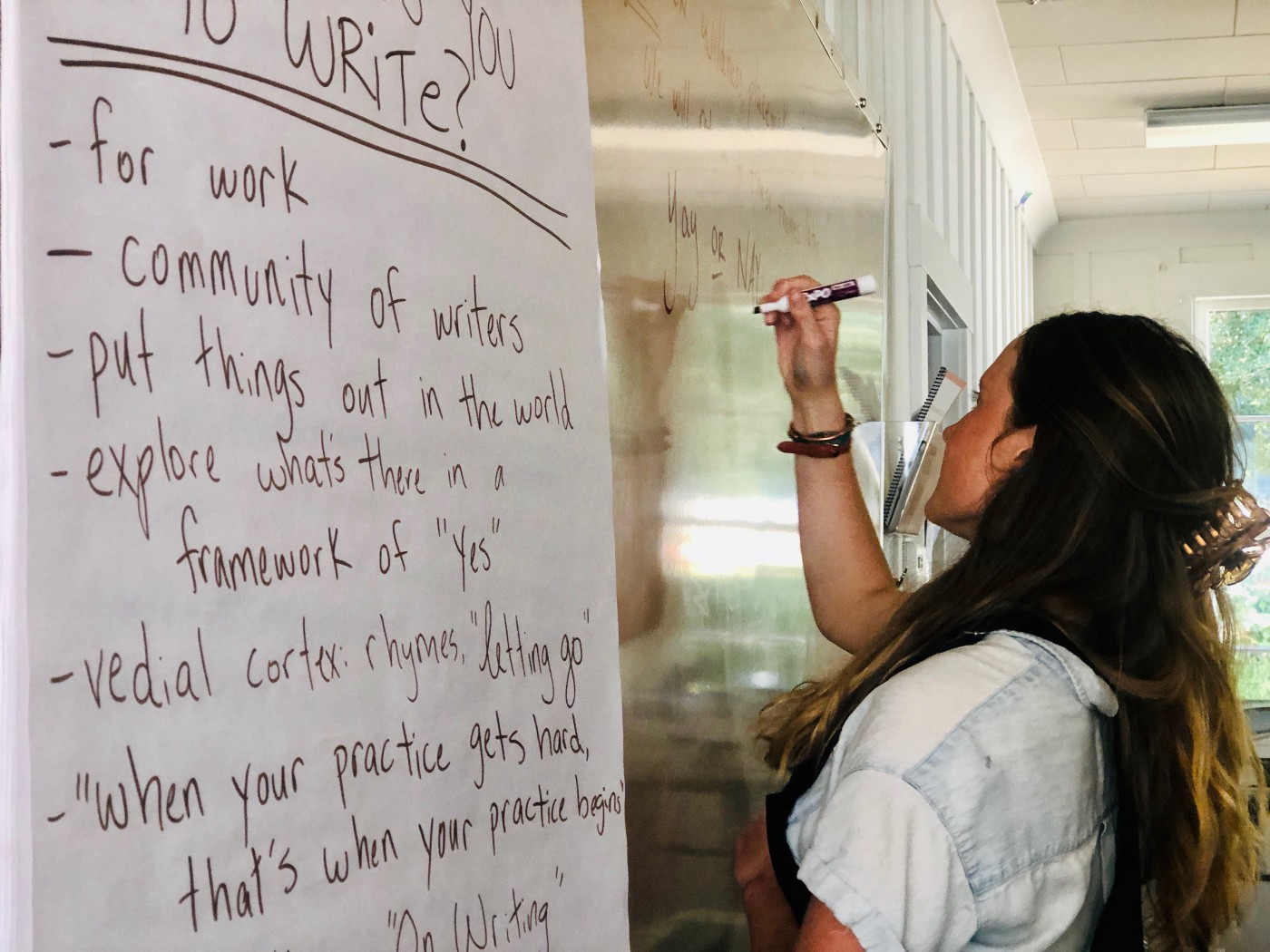 Woman in front of whiteboard brainstorming ideas around writing.