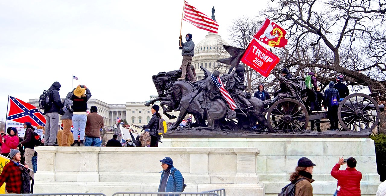 """Trump supporters stand on and around the Ulysses S. Grant monument on 6 January 2021, with the US Capitol building in the background, displaying flags including the US flag, the Confederate navy jack, Gadsden flags, the Bedford flag, and a """"Trump 2020"""" flag."""