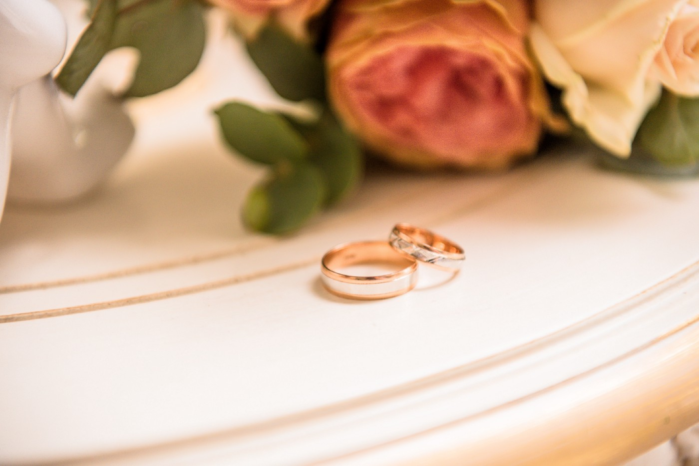 Two wedding rings on table with roses in background.