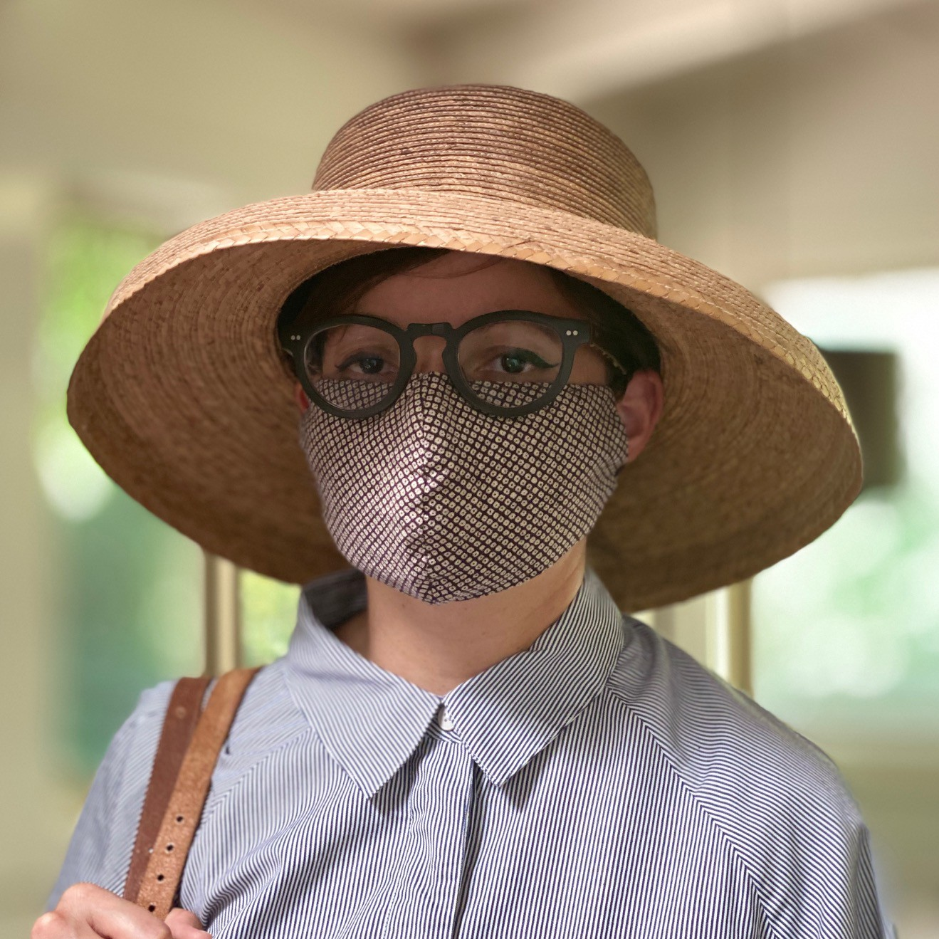 A person wearing a button-up shirt, round glasses, a wide-brimmed straw hat, and a face mask with a diamond pattern.