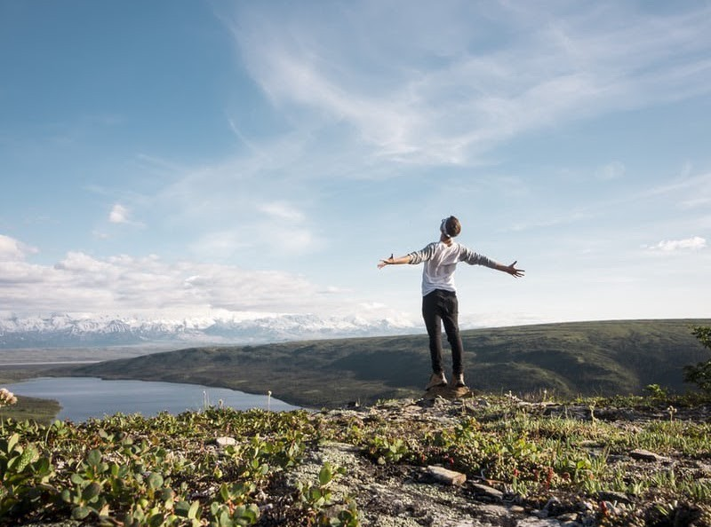 Person standing on hill overlooking lake with arms outstretched.