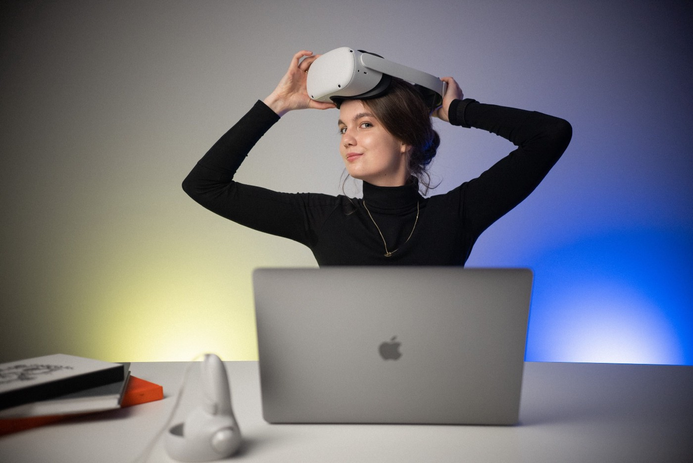 The author—young girl—behind her laptop wearing the Oculus VR headset, smiling.