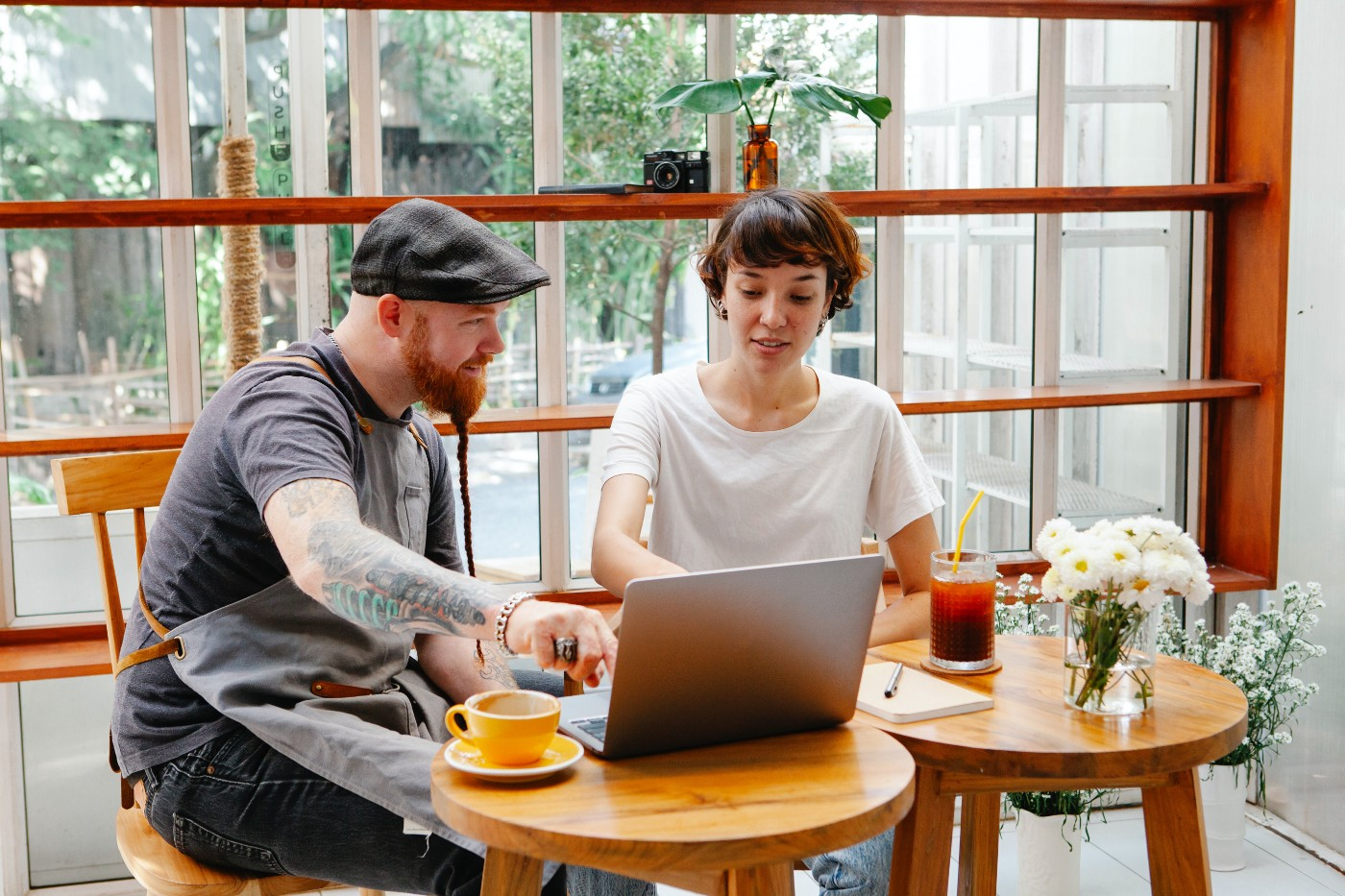 A man and a woman working on a laptop at a table.