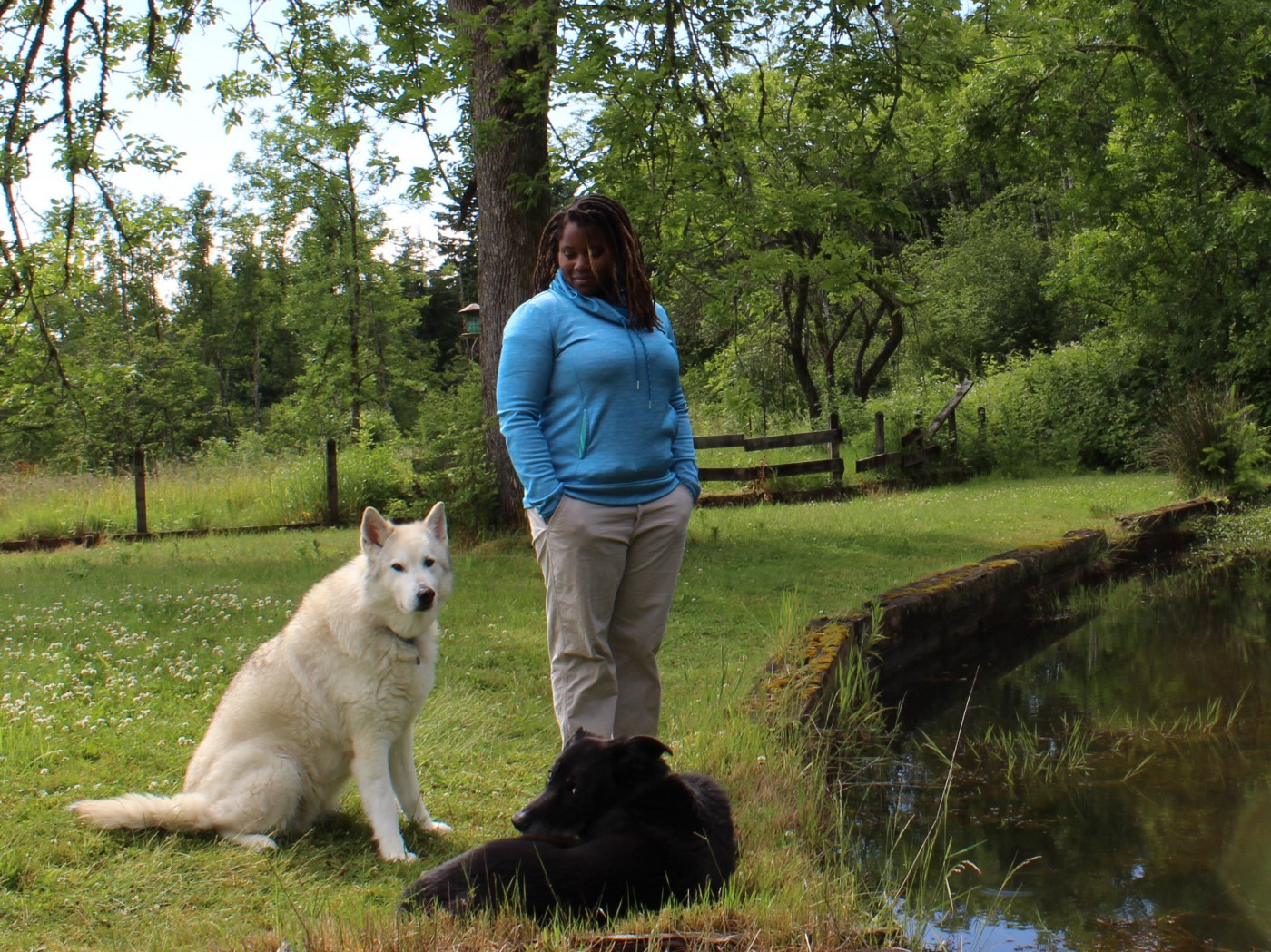 Nicole and her dogs near the edge of her pond. One dog is black and the other is white. Photo credit: Nicole Hams