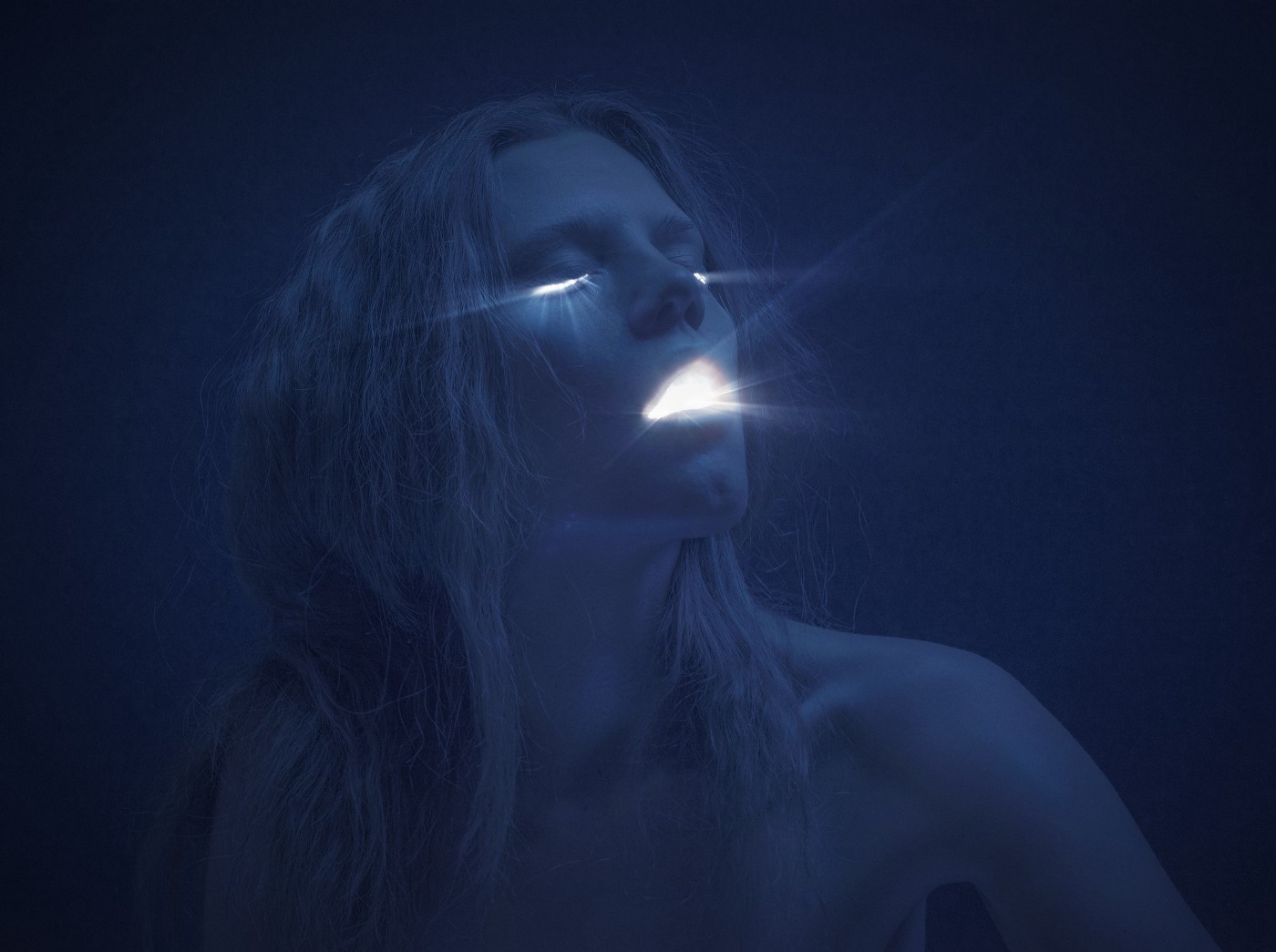 A photo of a woman with light shining from her eyes and mouth. The image is a dark blue/black shade.