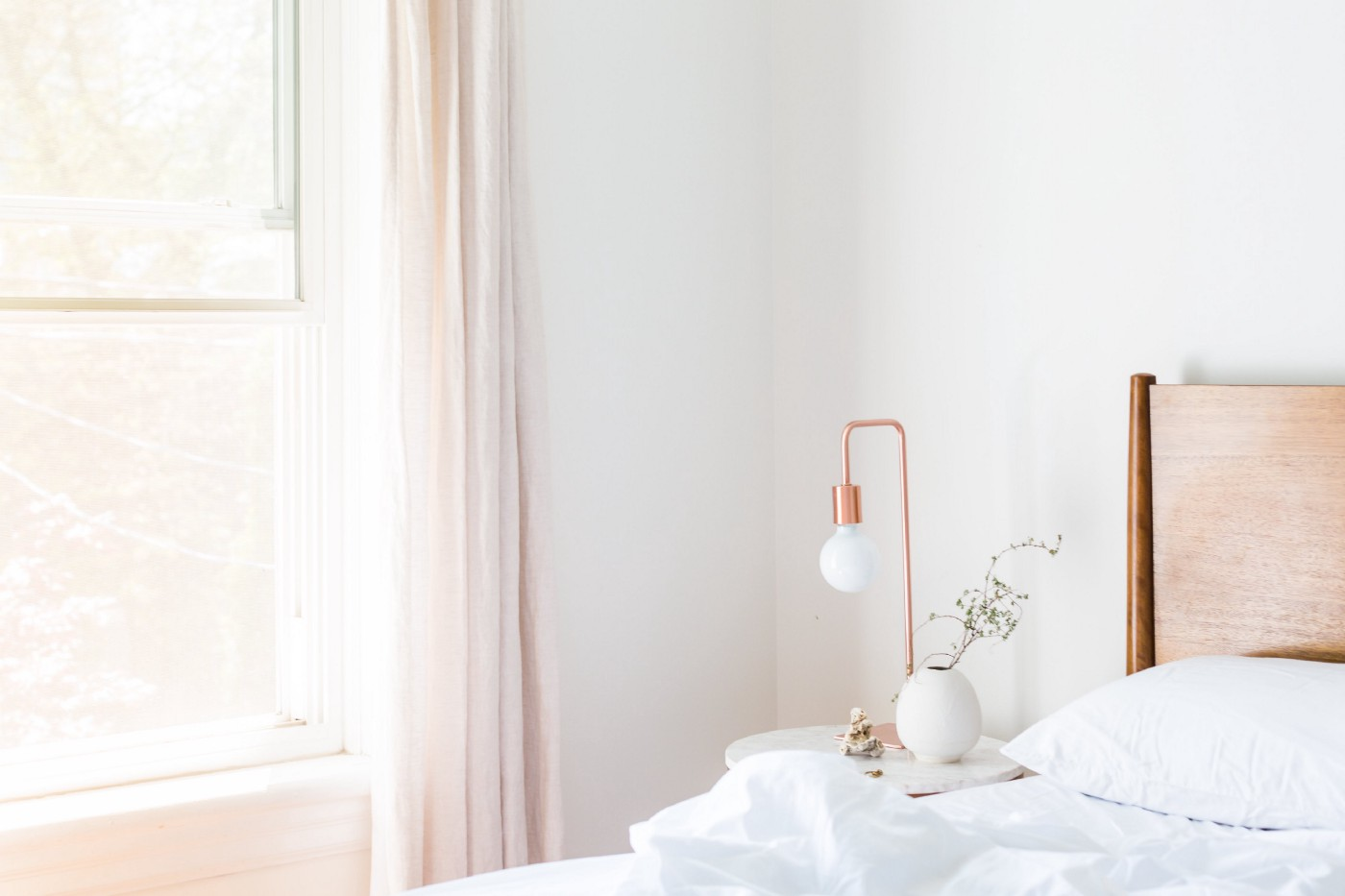A light-filled bedroom with a bed with white sheets and a side table with a copper accent light and a plant.
