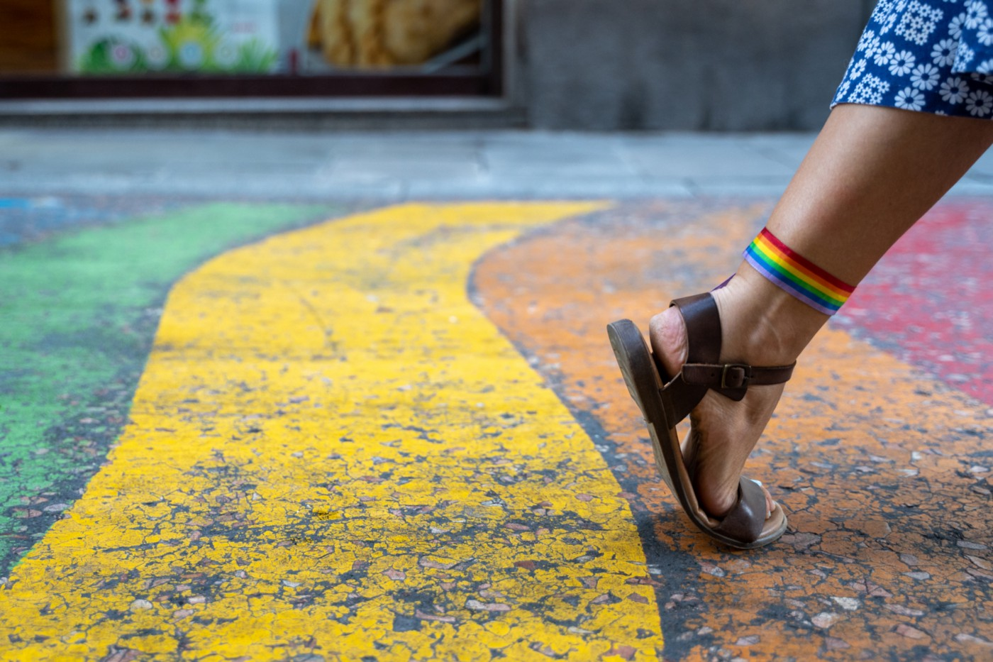 A woman's foot with sandals and a rainbow flag tied to the knuckle making a step forward on a rainbow sidewalk.