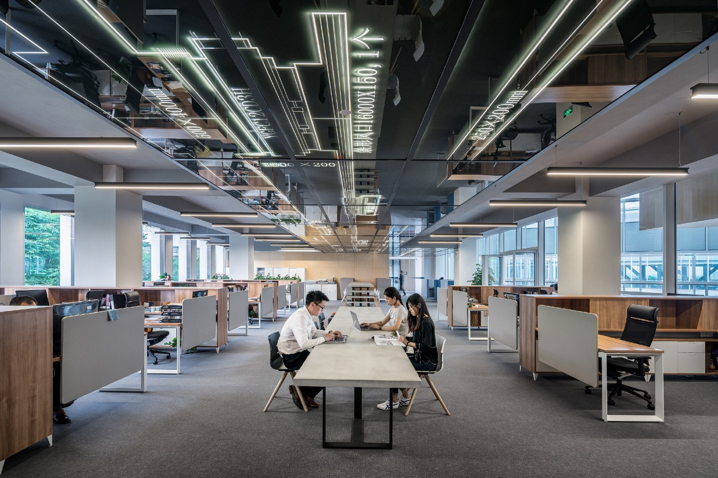 man and woman sit at a table in an open, modern office