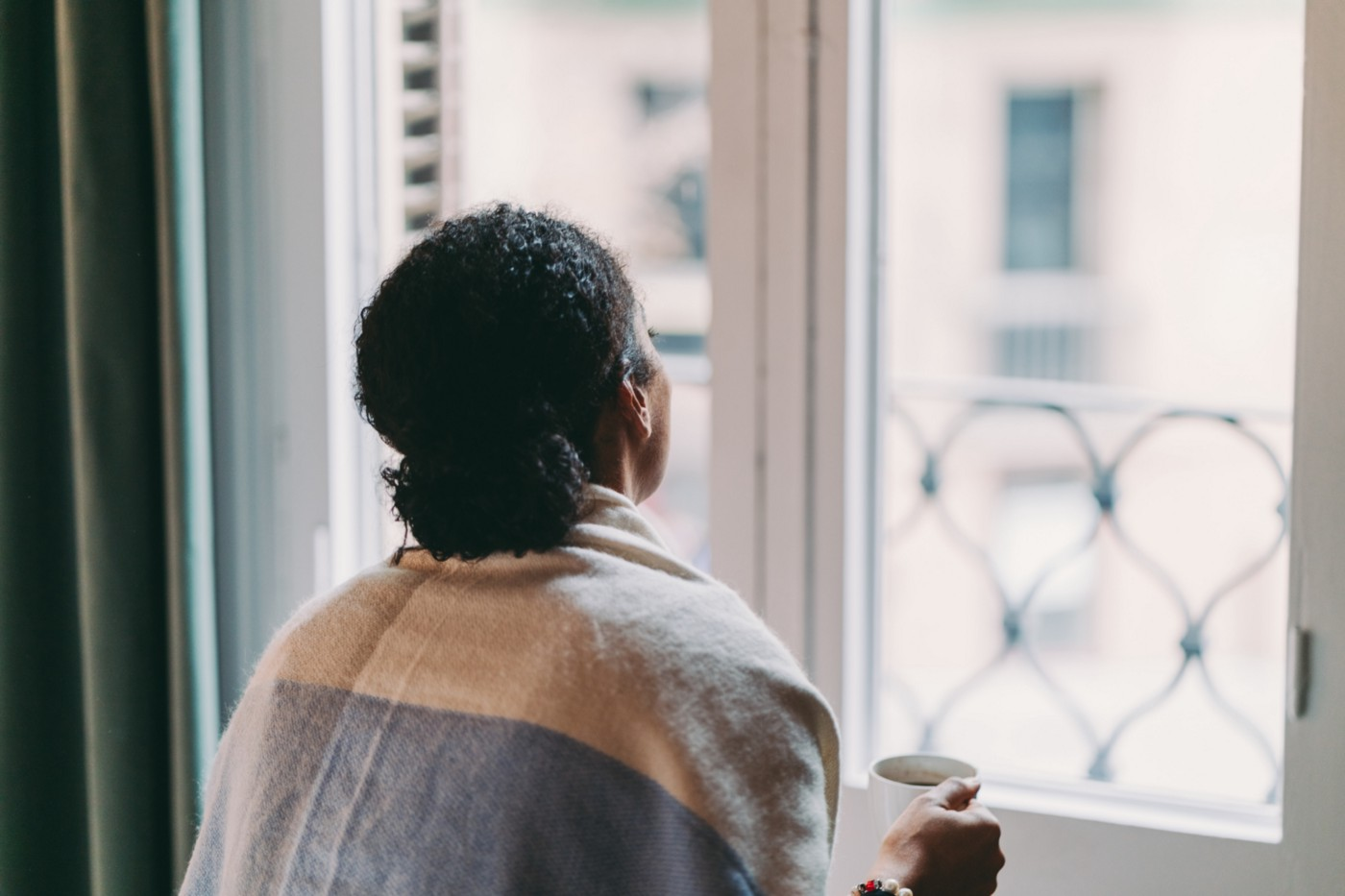 Black woman holding a cup of coffee while looking out her window.