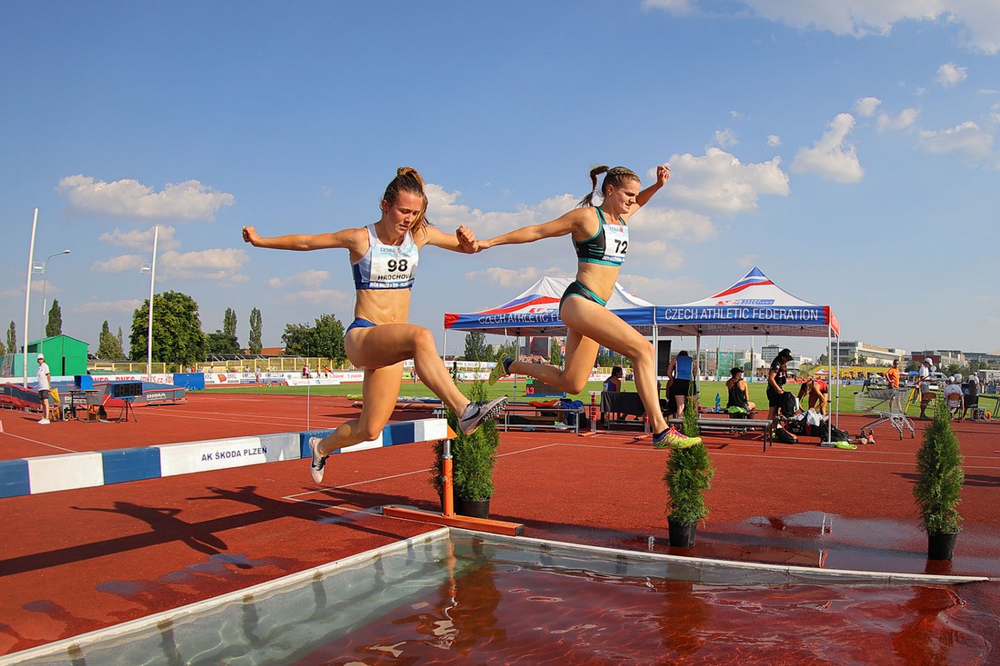 An action shot: Tereza (author) and another runner jump over a water pit during the 3000 meter steeplechase.