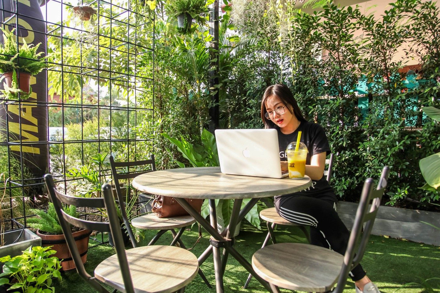 Woman sitting at a table, working on her laptop. She is on a lawn, surrounded by plants and small trees in an indoor/outdoor hybrid setting. She has a yellow beverage next to her laptop.