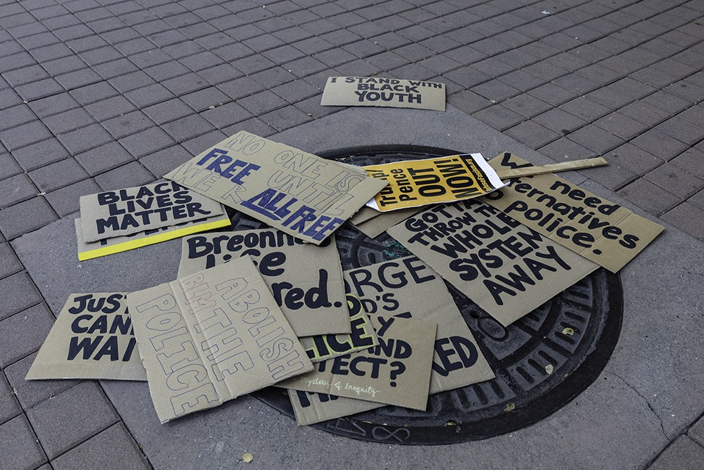 Protest signs from Oakland's 2020 Juneteenth protest litter the ground of Frank Ogawa Plaza