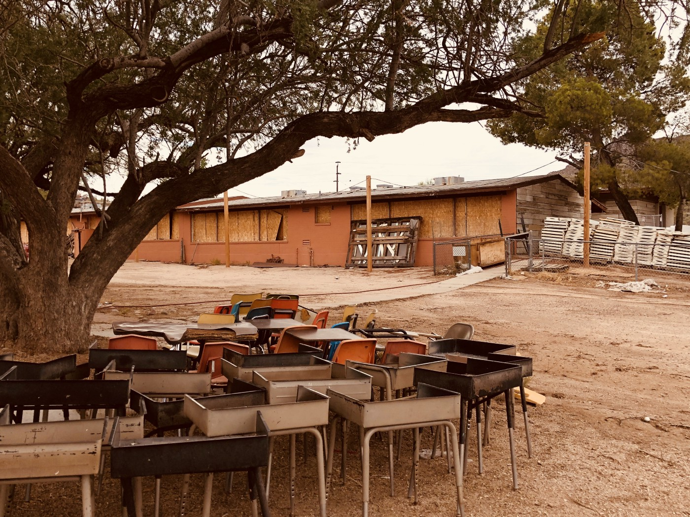 Photo of author's childhood elementary school, now boarded up with an abandoned circle of desks discarded beneath a tree