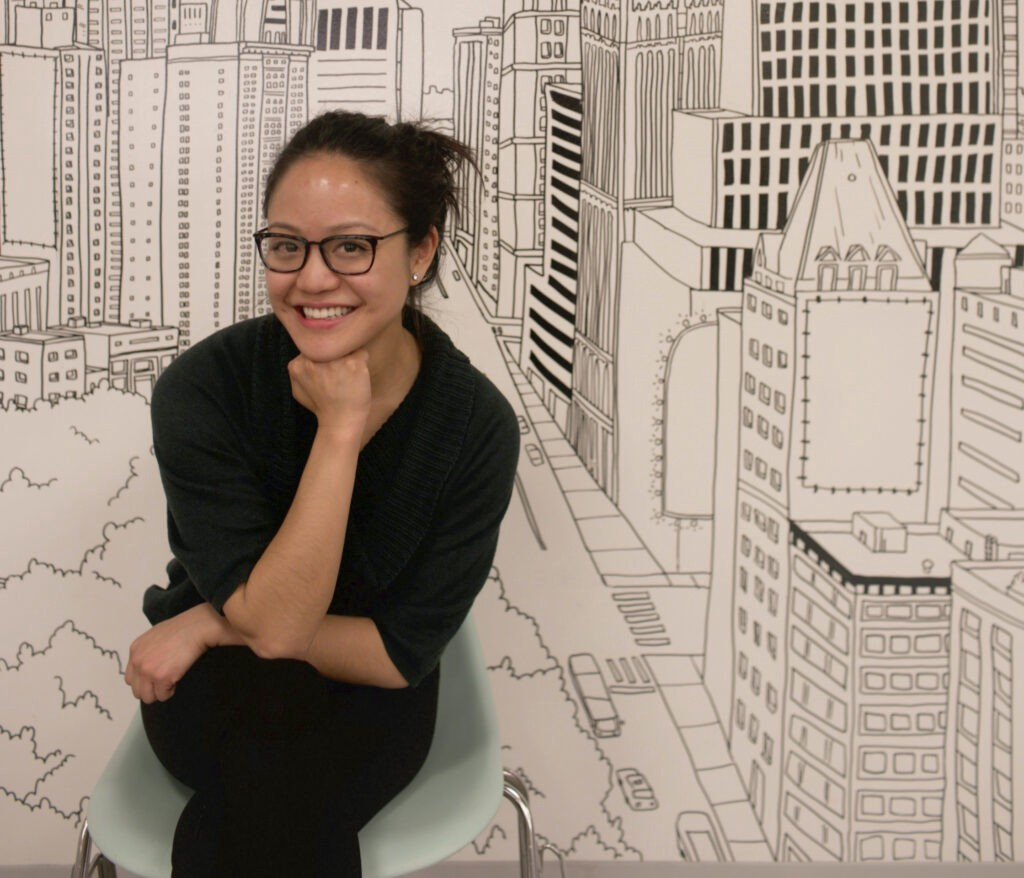 Lynne Guey sitting in front of a sketch of New York City