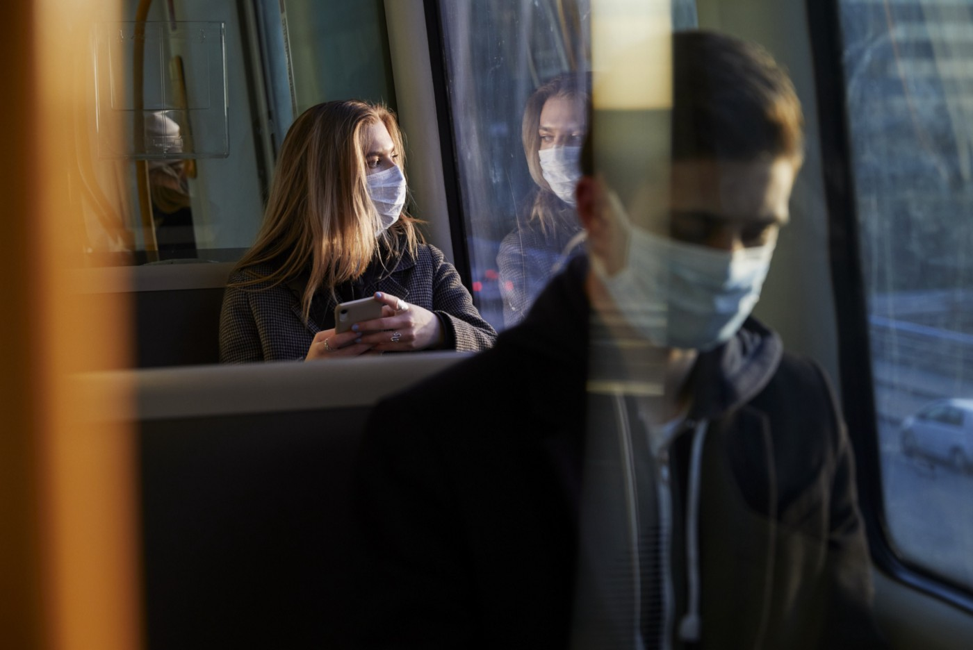 Young people on train wearing face masks.